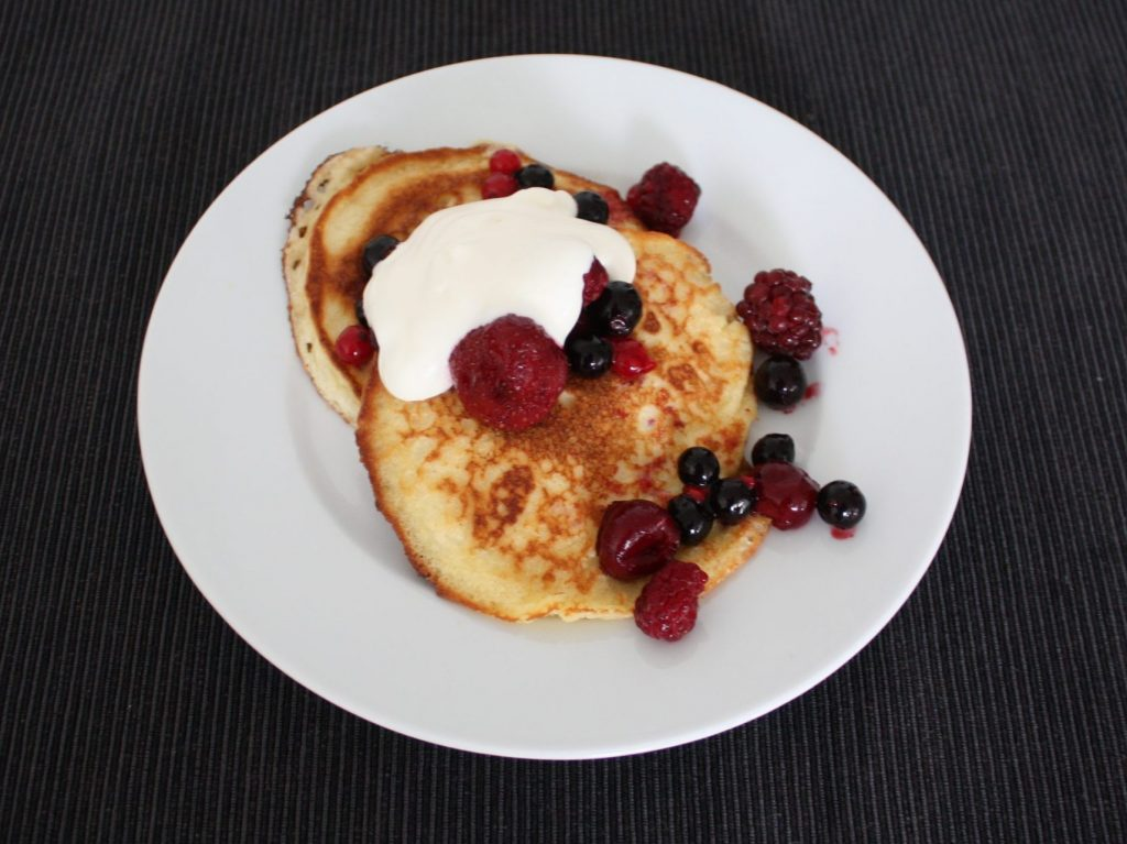 Delicious pancakes with berries and cream